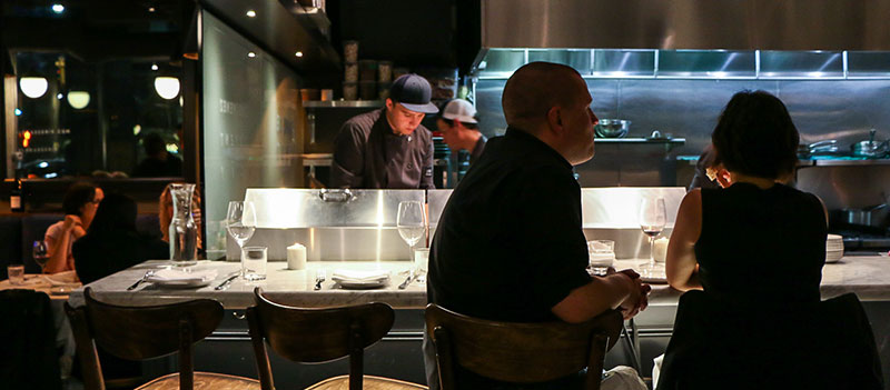 People in an open concept kitchen restaurant