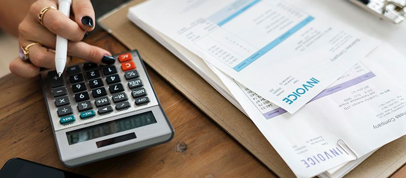Person using calculator and paying invoices