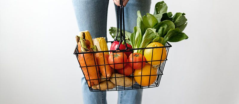 Person holding basket full of produce and groceries