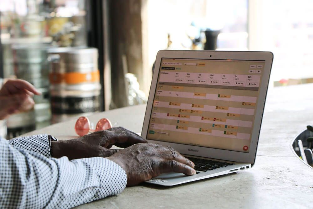 Restaurant worker using laptop with scheduling software.